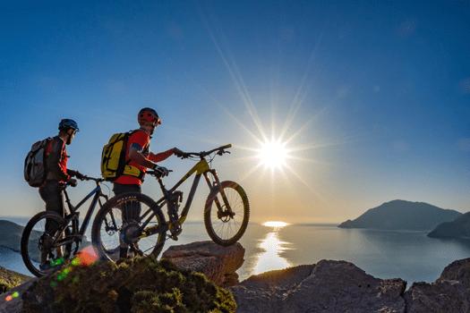 Mountainbiker bei Sonnenuntergang an Küste